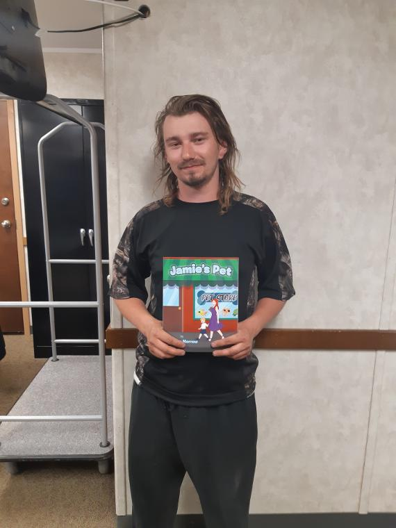 Ryan Frost Takes A Picture Holding Jamie's Pet Children's Book