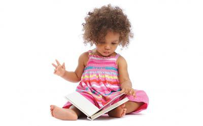 Black Toddler Girl Sitting Reading Book in Pink Dress