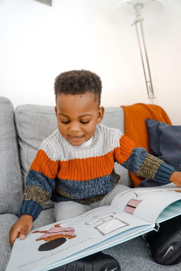 Black Toddler Boy Reading Book on Couch
