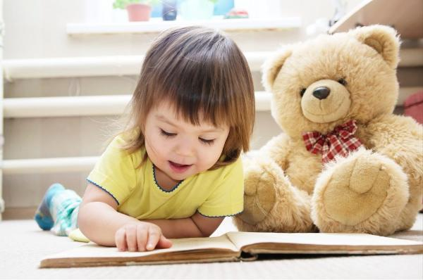 Toddler Reading Book on Floor with Teddy Bear